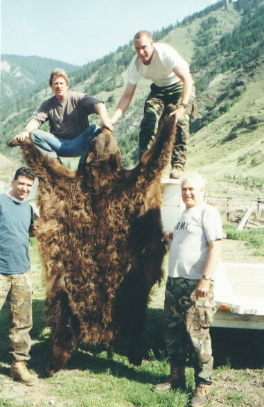 Several hunters pose with a black bear hide, harvested in the Selway Bitterroot Wilderness area with York Outfitters