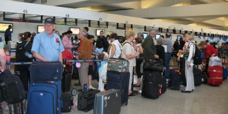 Check in line at airport with many passengers and their luggage