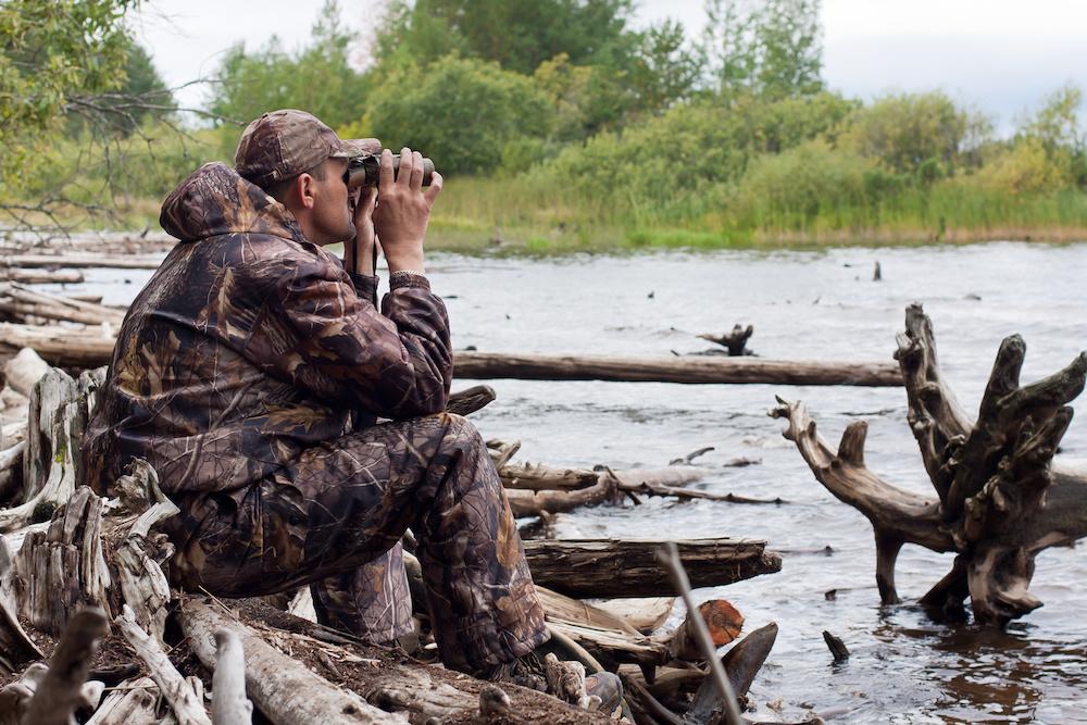 sitting hunter with binoculars