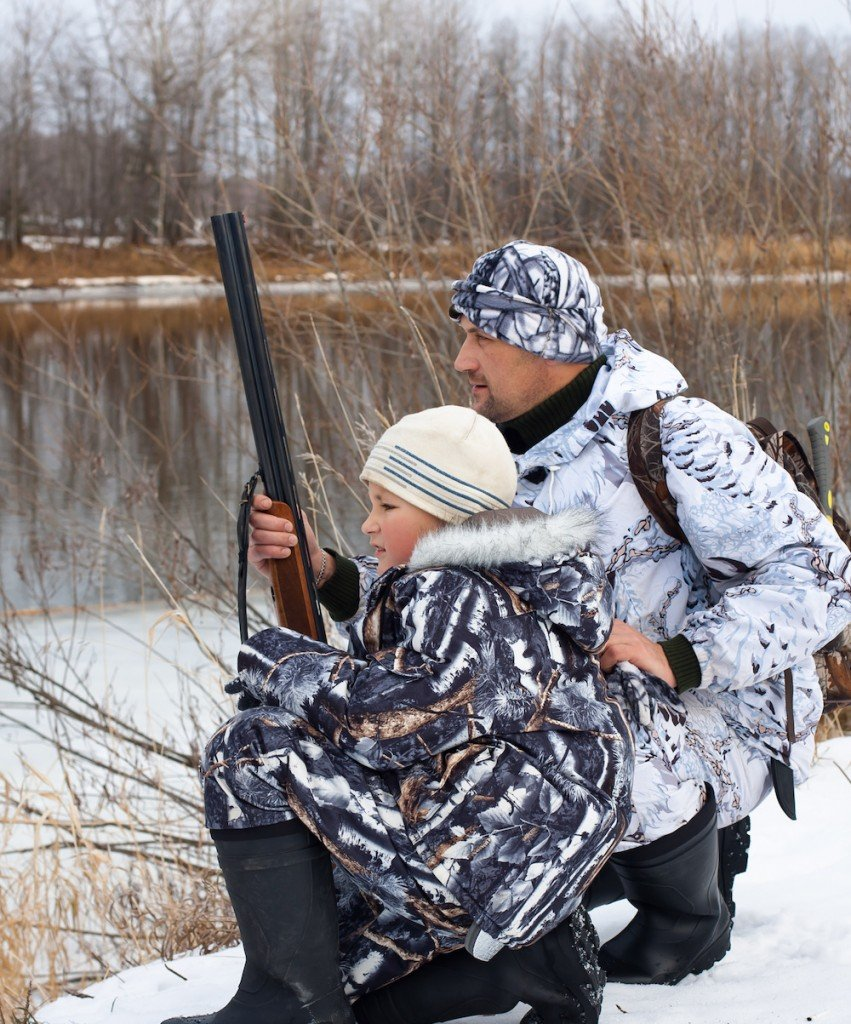 hunter with his son on the riverbank during winter hunting