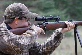 Supporting a rifle while shooting on shooting sticks